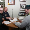 Aaron Costic, on the right, owner of this ice sculpture company, is reviewing the ice sculptures' contractual agreements with two of the eight partipants.