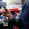 HOLLY PELCZYNSKI - BENNINGTON BANNER Mechanic, Keith Nichols holds a wifi bluetooth enabled plug that communicates with vehicles and and a state inspection ipad app during an inspection at Len Nichols & sons auto repair shop on Main St. in Bennington on Thursday afternoon.