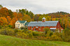 Fall foliage and farm with red barn in rural Vermont, USA.