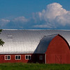 A red barn with cluds and blue sky