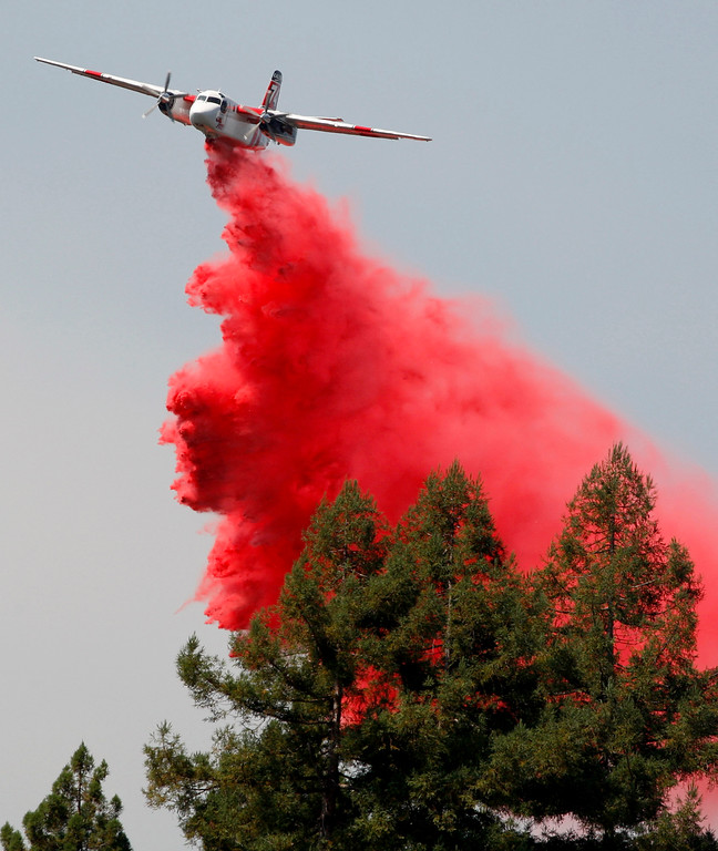 . A Cal Fire air-tanker makes a retardant drop on the wildland fire off Cox Road in Aptos on Wednesday, Aug. 30, 2017.  Cal Fire personnel along with a helicopter and two air-tankers held the fire to three acres.  (Vern Fisher - Monterey Herald)