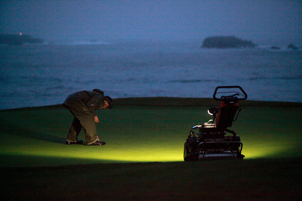 . Grounds crew member Manuel Flores prepares the 18th hole at the Pebble Beach Golf Links during the pre dawn hours for the second round of the AT&T Pebble Beach Pro Am on Friday, Feb. 10, 2017.   (Vern Fisher - Monterey Herald)