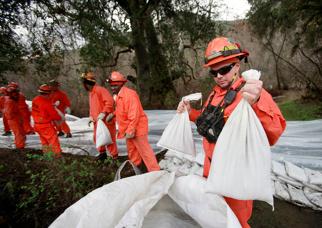 . A Cal Fire work crew  place sand bags on the bank of the Carmel River near Paso Hondo Road on Wednesday, Jan. 11, 2017.   (Vern Fisher - Monterey Herald)