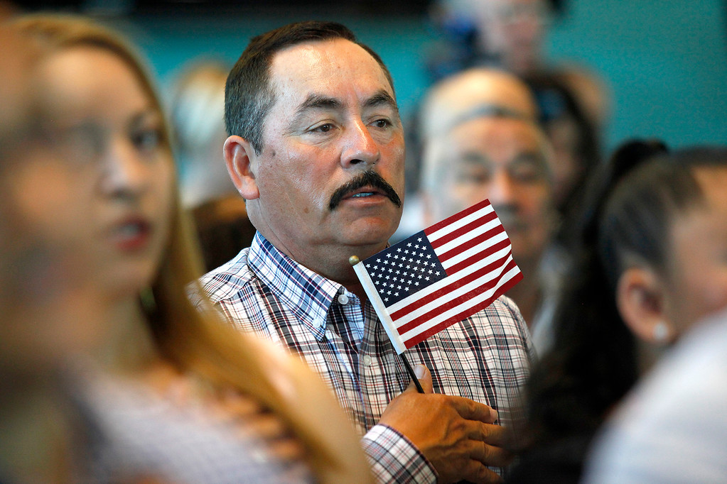 . A man from Mexico who became a U.S. citizen holds an American flag while taking the oath during the naturalization ceremony at the Cesar Chavez Library in Salinas on Friday, March 31, 2017.  (Vern Fisher - Monterey Herald)