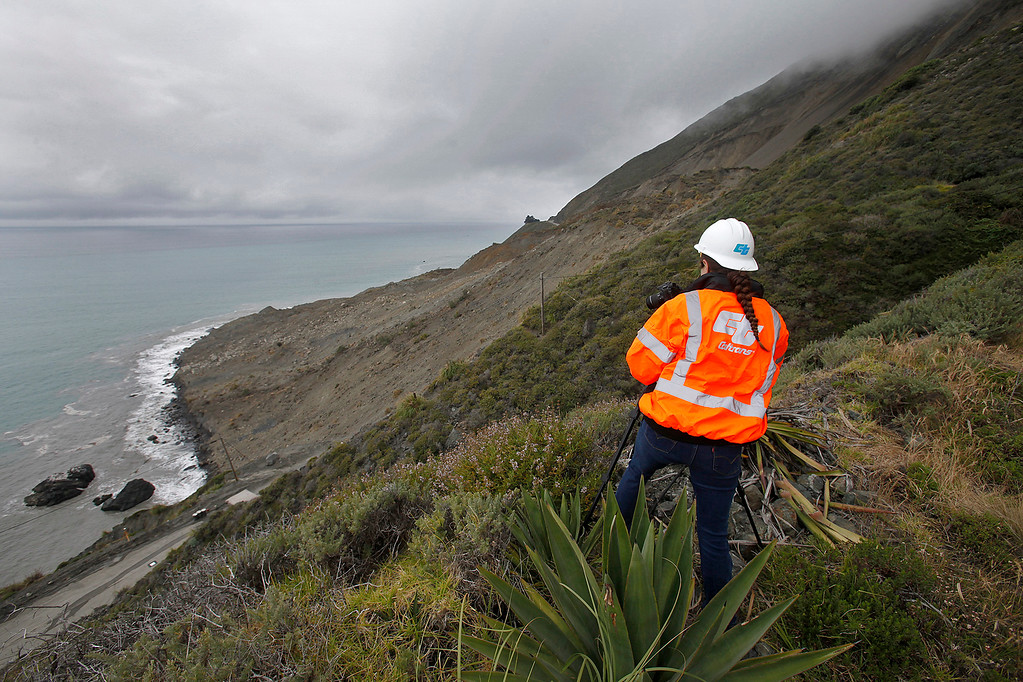 . Cal Trans public affairs officer Jessica Biro photographs the southern end of the Mud Creek slide as it covers Highway One in southern Monterey County on the Big Sur coast on Thursday, May 25, 2017.  (Vern Fisher - Monterey Herald)