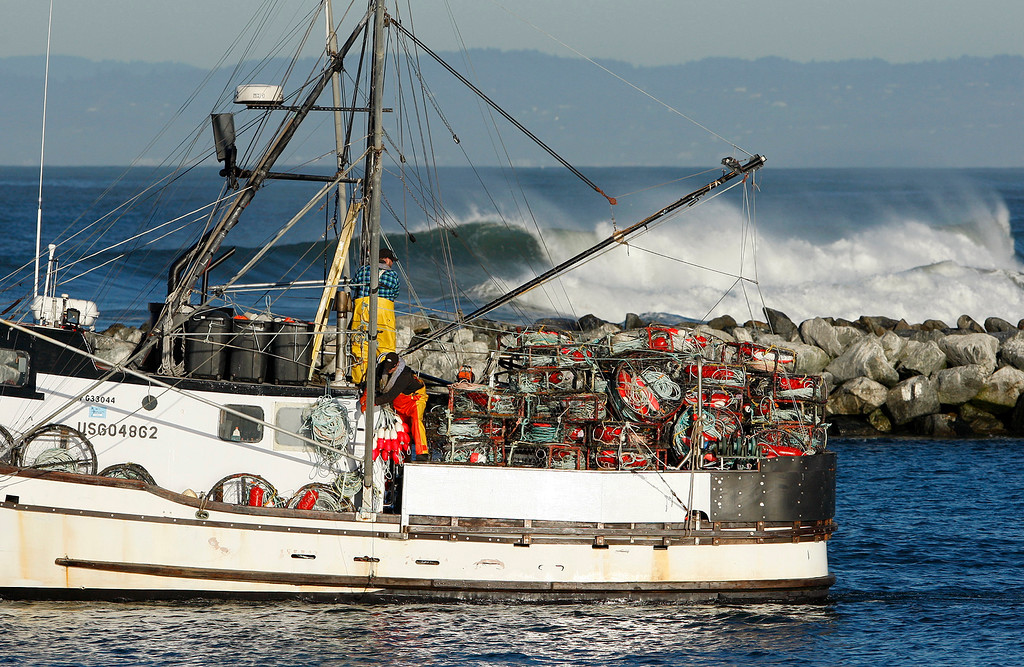 . Crew members on the commercial vessel Clipper III secure crab pots as they motor out of the Moss Landing Harbor during a big swell on Thursday, Nov. 30, 2017.  (Vern Fisher - Monterey Herald)