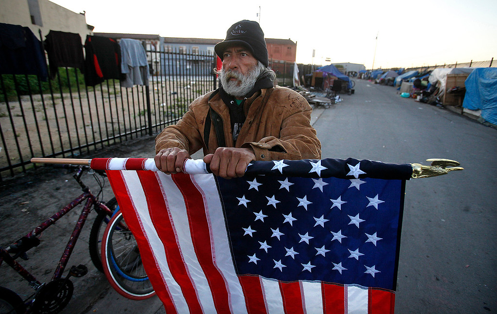 . Homeless person Art Espinoza packs his American flag prior to the homless sweep in the Chinatown district of Salinas on Wednesday, March 23, 2016.  (Vern Fisher - Monterey Herald)