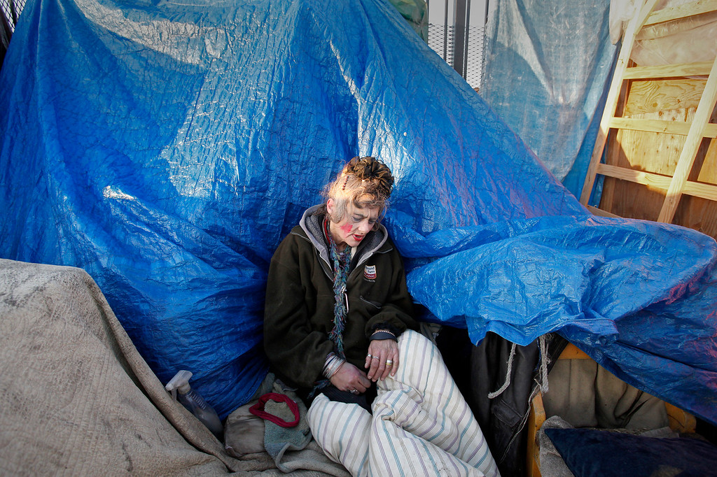 . A homeless woman at her tent prior to the homless sweep in the Chinatown district of Salinas on Wednesday, March 23, 2016.  (Vern Fisher - Monterey Herald)