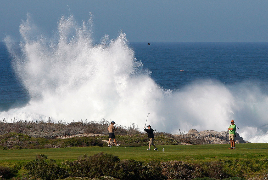 . Golfers at Pacific Grove Golf Links as large waves crash on Point Pinos on Friday, Nov. 4, 2016.  (Vern Fisher - Monterey Herald)