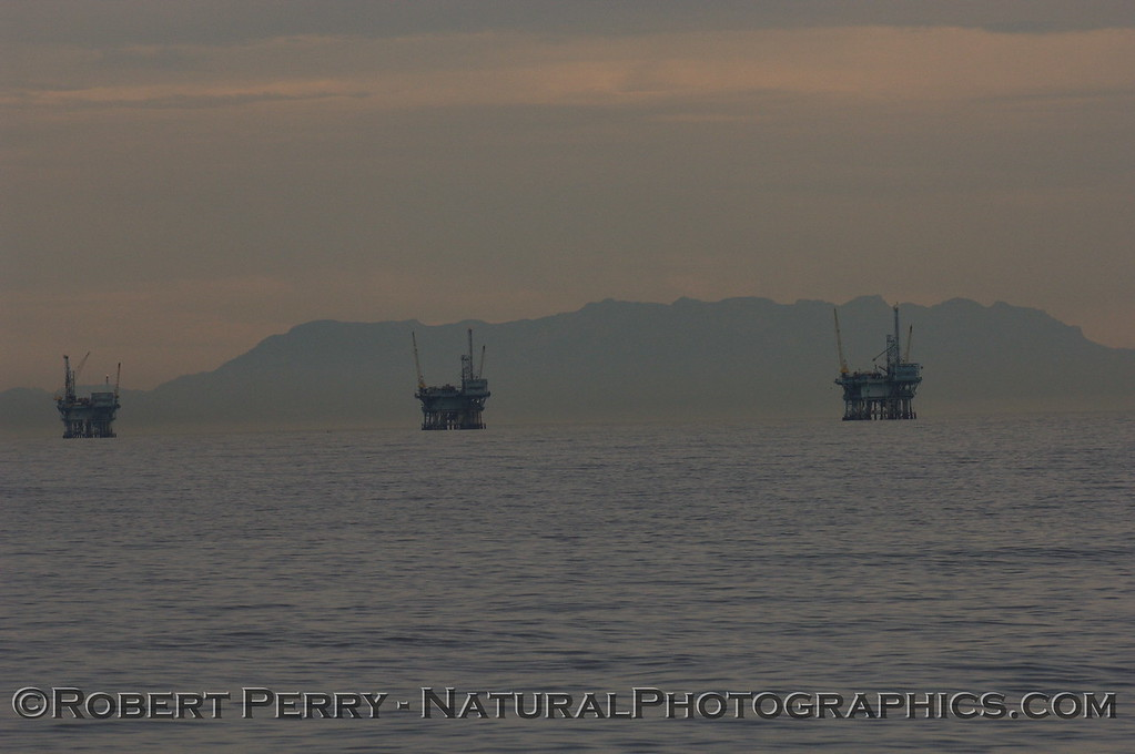 Silhouettes of Platforms in the Santa Barbara Channel in morning light.  Boney Ridge above Malibu can be seen in the background.