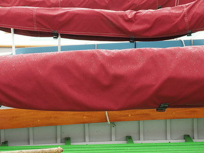 Main sail covers on a trio of dinghies.