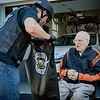 At left, Forged Alliance biker, Tom Roy of Pelham gives Korean War Veteran, George Werber, 87, of Westford a biker vest to wear on his surprise motorcycle ride to Kimball Farm. SUN/Caley McGuane