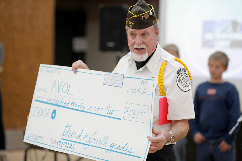 Charlie Nash holds up a check given to Associated Veterans of Loveland by the third and fourth graders at Big Thompson Elementary on Tuesday, Nov. 10, 2015 in Loveland. (Photo by Trevor L. Davis/Loveland Reporter-Herald)