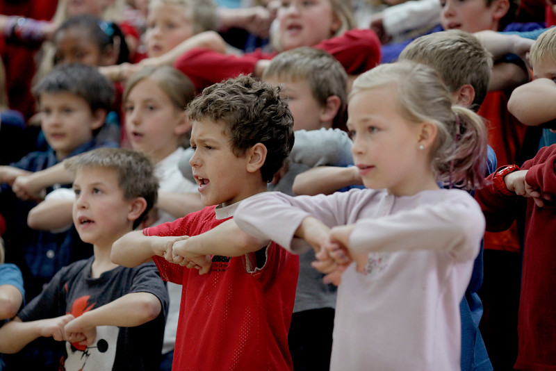 Michael Entzi, left, and Alex Gill-French sing and dance along to patriotic songs with third and fourth graders at Big Thompson Elementary School on Tuesday, Nov. 10, 2015 in Loveland. (Photo by Trevor L. Davis/Loveland Reporter-Herald)