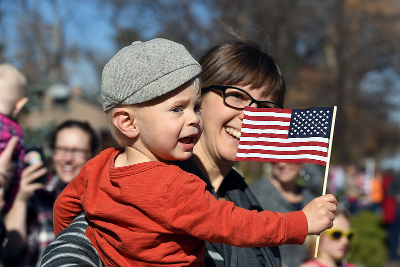 Daniel McLaughlin of Loveland, 2, waves an American flag as his mom, Erin McLaughlin holds him during the Veterans Day parade Friday, Nov. 11, 2016, in Loveland. (Photo by Jenny Sparks/Loveland Reporter-Herald)