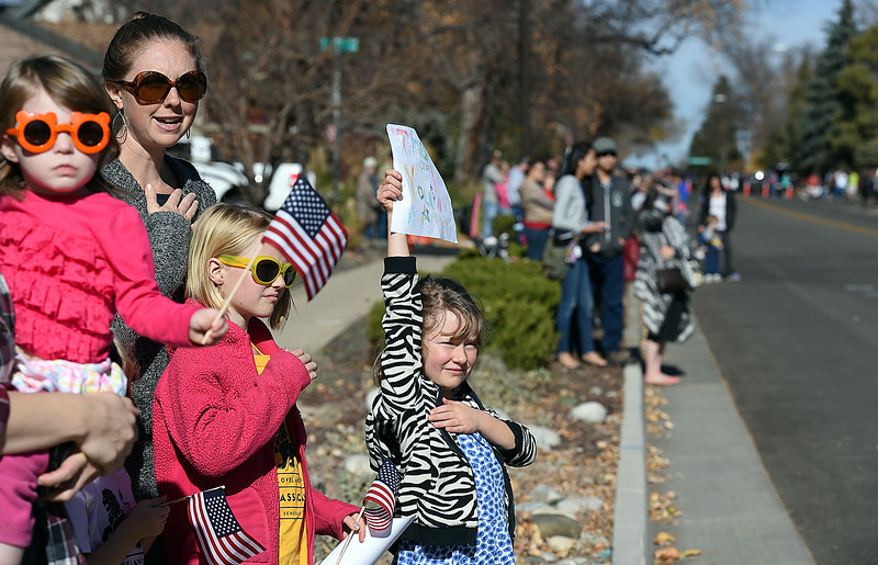 Anna Kemp, 6, center, holds a hand-made thank you sign for veterans during the Veterans Day parade Friday, Nov. 11, 2016, in Loveland. With Anna from left are Adalynn Feaver, 2, Carisa Kemp, and Lea Kemp, 9. (Photo by Jenny Sparks/Loveland Reporter-Herald)