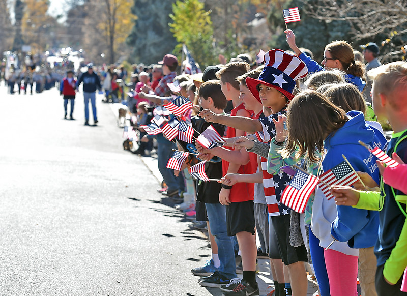 Wearing a patriotic hat and shirt, Namaqua elementary School fifth-grader Karsten Lewis, 10, and classmates wave American flags as the Veterans Day parade makes its way up Garfield Avenue Friday, Nov. 11, 2016, in downtown Loveland. (Photo by Jenny Sparks/Loveland Reporter-Herald)