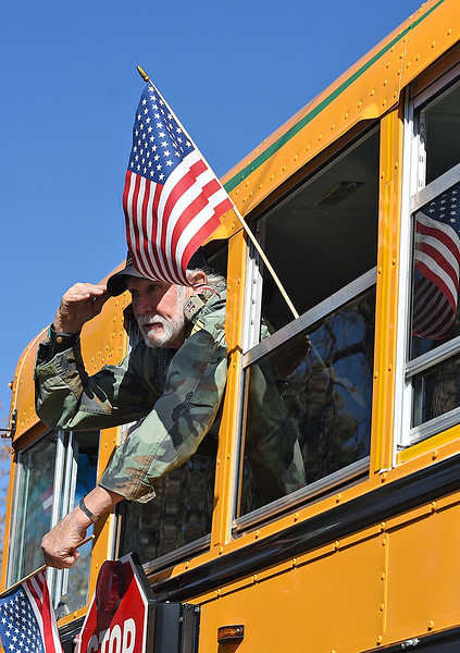 U.S. Army veteran Kit Kittinger salutes to other veterans while riding in a school bus during the Veterans Day parade Friday, Nov. 11, 2016, in Loveland. (Photo by Jenny Sparks/Loveland Reporter-Herald)