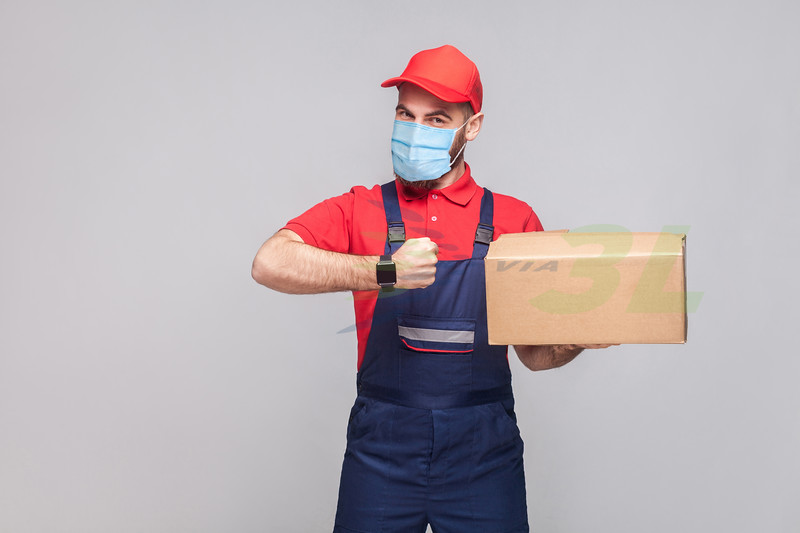 Delivery on quarantine. Ontime service! man with surgical medical mask in blue uniform and red t-shirt standing, holding delivery box and showing watch on grey background. Indoor shot, isolated,