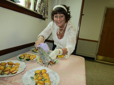 Power of Flowers Project volunteer Christine Folta sprinkled fresh rosemary over the savories at the Victorian tea. Photo by Mary Leach