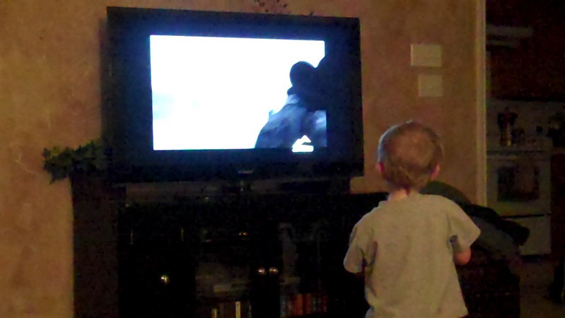 Kyle duck hunting on TV with his toy shotgun.