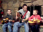 Scott gives Mason and Jake a lesson on their new guitars.