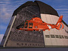 coast guard HH-65 Dolphin helicopter hovering next to Hanger One at Moffett filed Mountain View, California.