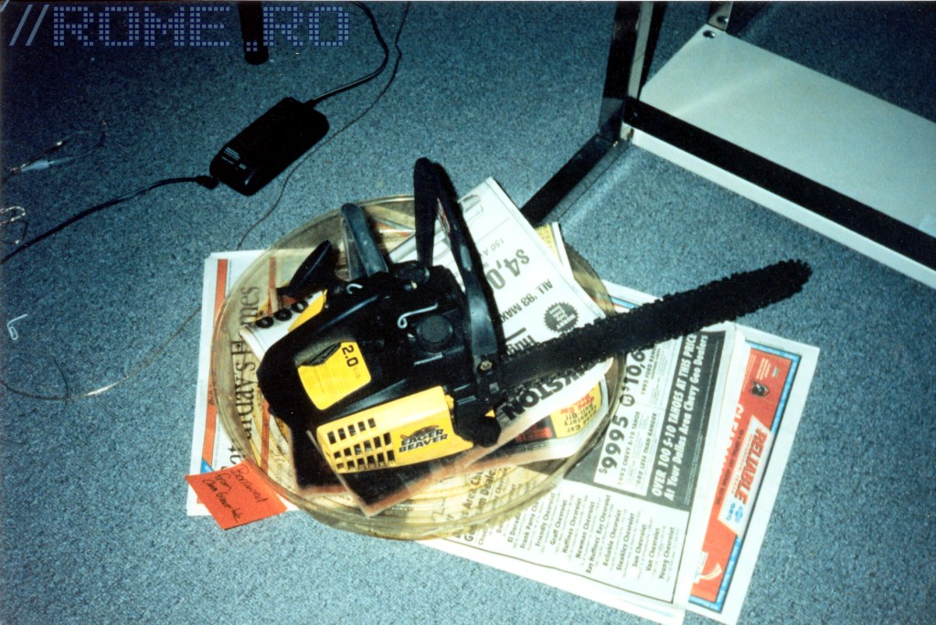 """This picture was taken during DOOM development in 1993. This is the DOOM chainsaw sitting in a bucket, ready to be scanned by Kevin to create the image of the chainsaw in DOOM. The reason it's in a bucket is because it leaked oil! That's also why there's newspapers all around it. :) Heh heh, yes, the name of the chainsaw was Eager Beaver. The little Post-It Note next to the chainsaw says """"Borrowed from Ann Graver Holz"""". Ann was Tom Hall's girlfriend at the time and since she had a chainsaw (Most of us apartment-dwellers did not own a chainsaw!), she let Tom borrow it. Tom, um, forgot to give it back to her.....so........it's still around. Tom is going to do something with it, probably sometime this year!"""
