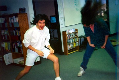 Both Shawn Green and myself are big heavy metal maniacs!  During DOOM we used to listen to lots of Alice in Chains, Black Sabbath, Judas Priest, Dokken, Metallica, etc. and here we are going crazy outside my office - HEADBANGING!    Yes, this is how nuts it was at id Software.  Just a short break between coding, mapping, and insane deathmatch screaming.  The rack of CDs are mine and Carmack's and that's my office you can see into.  That office door is the one Carmack blasted open with his axe.