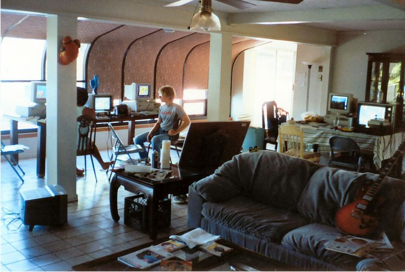 This is a picture of the Shreveport lakehouse that id Software started in.  Tom took this pic of John Carmack and me while we were working on the Super Mario 3 demo for Nintendo - so this was sometime in September 1990.  You can see how nice it was outside while we were inside just coding. Heh.  The computer setup on the far table was Tom's 386/33 and a TV set hooked up to a VCR that had a videotape of Super Mario 3 freeze-framed so he could duplicate the graphics pixel-by-pixel.  The TV between John and I was hooked up to an NES so we could play SM3 and watch the movement and how things worked so we could duplicate it.  There's a whiteboard propped up with writing on it that detailed all the tasks we needed to do to finish the demo.  During this time there was a lot of summer flooding around the lake and one day I actually waded through a ton of water up to my waist to get to id to keep coding.  Lucky for me I didn't run into any snakes!