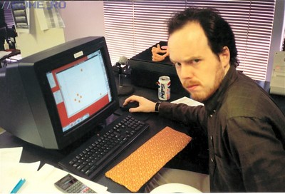 """This picture was taken during DOOM development in 1993. Tom's busy working on a map in my map editor, DoomEd, but don't worry - you won't be able to make out anything on the screen! Tom started many of the original DOOM maps and after he left, Sandy Petersen finished them -- some of the maps had very little work done to them, in fact.  On Tom's monitor is a little printout that says, """"Quality"""". He always has notes stuck to his monitor to keep him reminded of .... things. That orange thing could very well be the very first keyboard wrist pad -- made by a friend of his back before you saw them in stores. The speaker at the far right is one of the first Altec Lansing clamshell models. The microphone in front of Tom was there for NeXTSTEP's awesome email feature - built-in voice emails! We always sent them back and forth... I think I might have some of them lying around here..."""