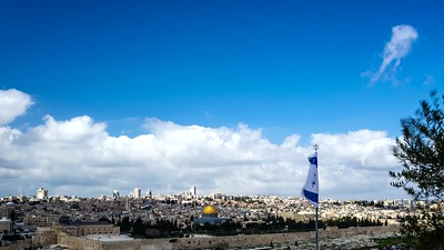 Israeli Flag with the view of Jerusalem on a cloudy day