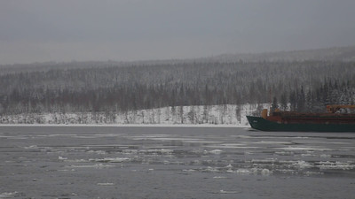 A ship moves through ice floes on a river