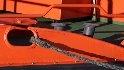 The red hull of a boat rocks on the waves