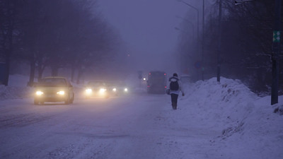 People and cars on a street on a foggy winter evening