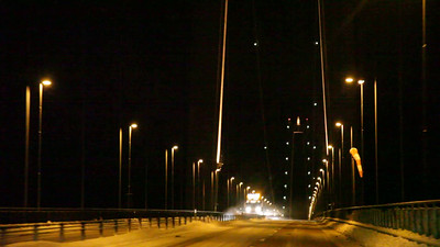 POV shot of a car driving over a suspension bridge at night