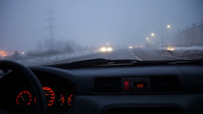 Driving on a motorway in cold and foggy weather in winter