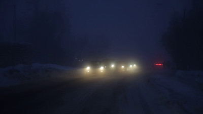 Driving through a winter night on a snow- and ice-covered road