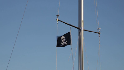 Pirate flag flapping on the mast of a sailing yacht.