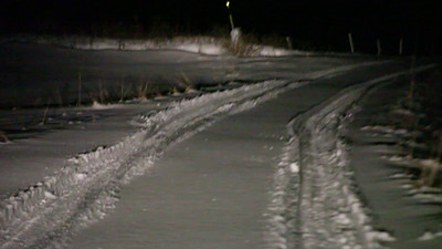 Driving on a snow-covered lane on a winter night