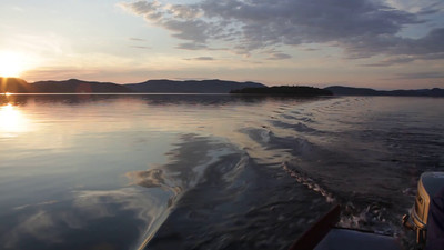 POV shot from a boat crossing a bay at sunset