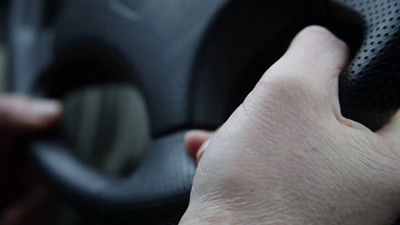 Hand holding the steering wheel of a car