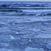 Ice floes floating and crashing against each other on ocean waves