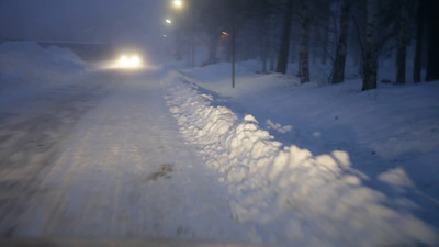 Driving on a snow-covered road on a winter evening