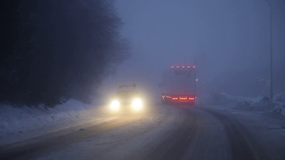 Driving behind a truck on a foggy winter evening on snow and ice
