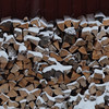 Snow falling on stacked fire wood