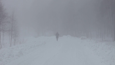 Woman jogging through the fog on a grey winter afternoon