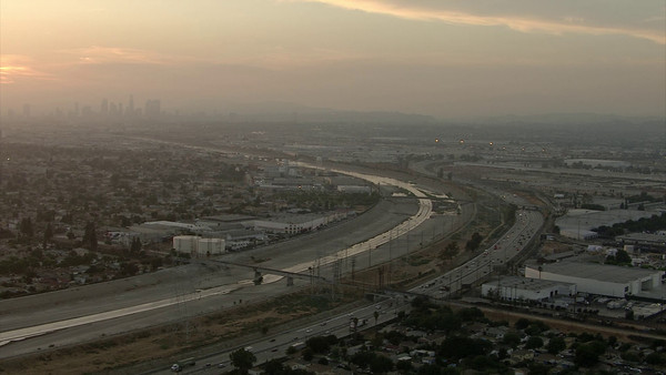 Flying down the LA River at Sunset with Downtown Los Angeles in the background.
