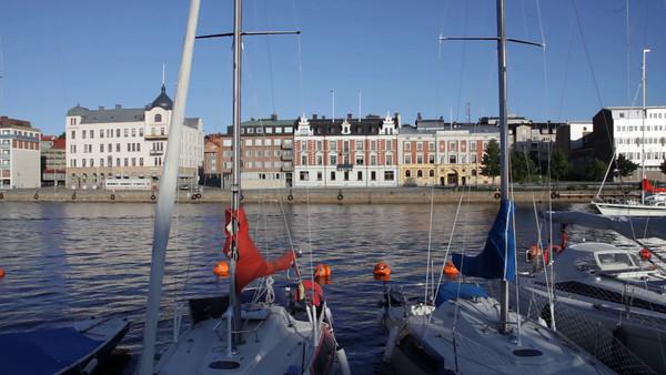 Härnösands gästhamn på sommaren -  A sailing yacht leaves a marina in Sweden