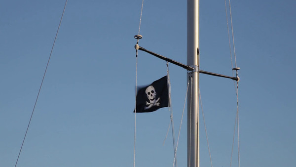 Härnösands gästhamn på sommaren -  Pirate flag flapping on the mast of a sailing yacht.